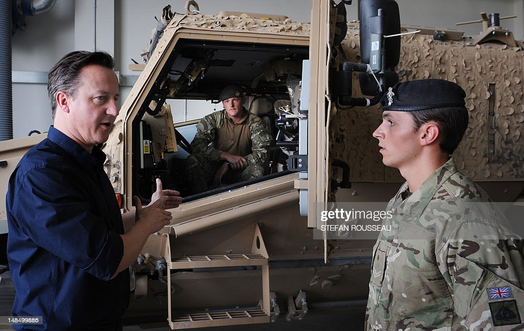 British Prime Minister David Cameron is shown a new 'Foxhound' armoured vehicle by British soldiers at Camp Bastion in Helmand Province on July 18...