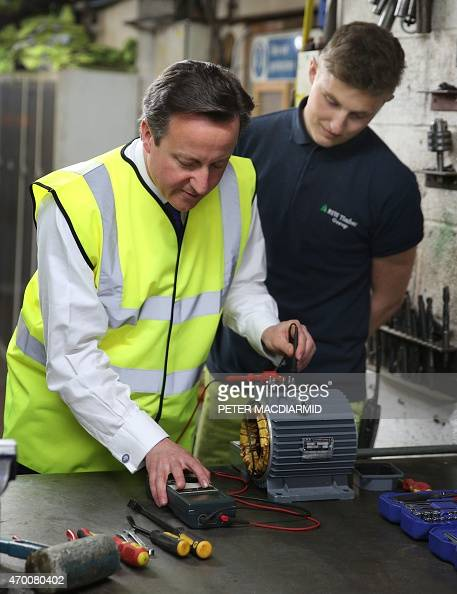 British Prime Minister David Cameron is shown how to test a circuit on a part by employee Tyler Evans during a visit to a timber yard on April 17...