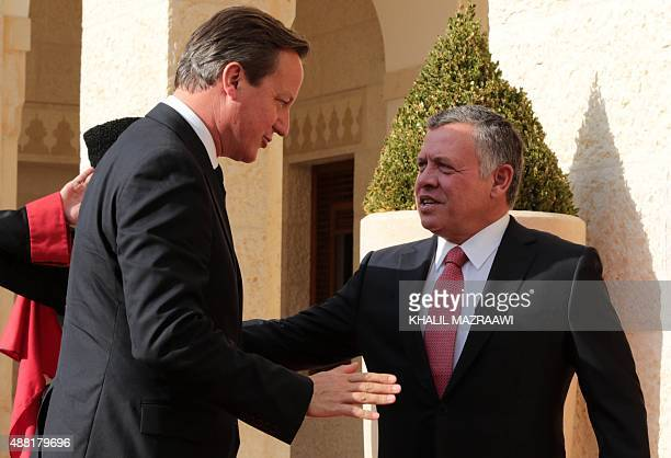 British Prime Minister David Cameron is welcomed by Jordanian King Abdullah II upon his arrival for a meeting at the Royal Palace on September 14...