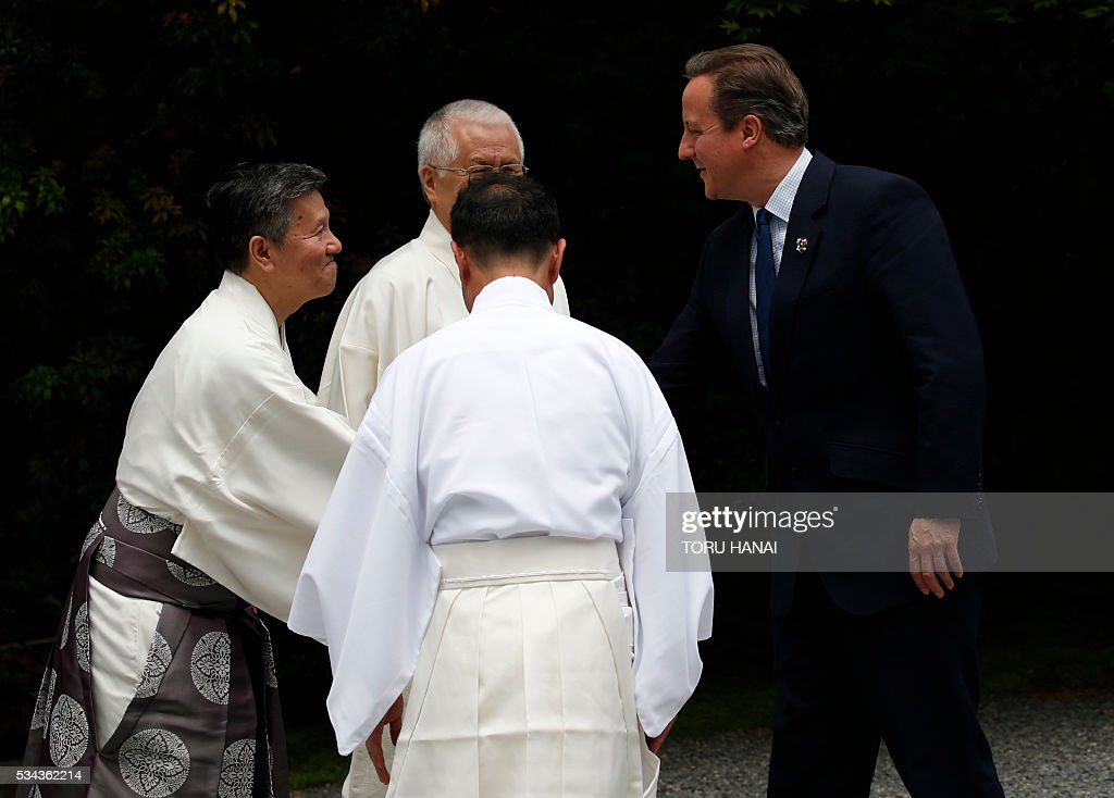 British Prime Minister David Cameron (R) is welcomed by Shinto priests as he visits Ise-Jingu Shrine in the city of Ise in Mie prefecture, on May 26, 2016, on the first day of the G7 leaders summit. World leaders kick off two days of G7 talks in Japan on May 26 with the creaky global economy, terrorism, refugees, China's controversial maritime claims, and a possible Brexit headlining their packed agenda. / AFP / POOL / TORU