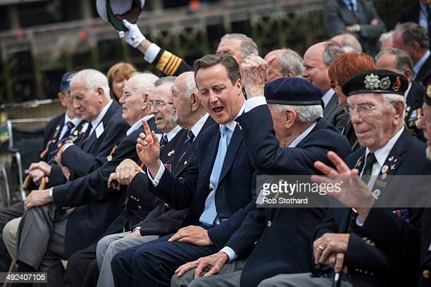 British Prime Minister David Cameron joins veterans aboard the HMS Belfast for the 70th anniversary DDay commemorations on May 20 2014 in London...