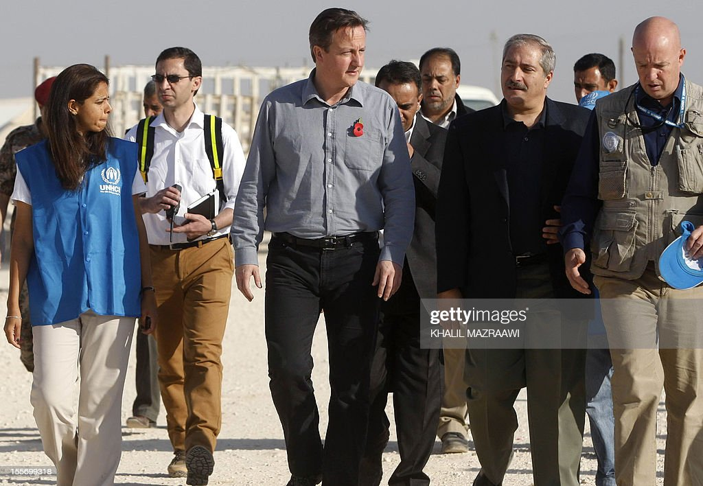 British Prime Minister David Cameron (C-L), Jordanian Foreign Minister Nasser Judeh (C-R) and United Nations High Commissioner for Refugees (UNHCR) representative to Jordan Andrew Harper (R) walk in the Zaatari refugee camp in the Jordanian town of Mafraq, near the border with Syria, on November 7, 2012. Cameron vowed to do more to help end the bloody crisis in Syria as he made a surprise visit to the sprawling Zaatari refugee camp following a three-day Middle Eastern tour.