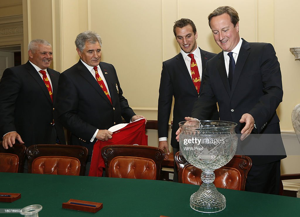 British Prime Minister <a gi-track='captionPersonalityLinkClicked' href=/galleries/search?phrase=David+Cameron+-+Politician&family=editorial&specificpeople=227076 ng-click='$event.stopPropagation()'>David Cameron</a>, (R) looks at the trophy as head coach <a gi-track='captionPersonalityLinkClicked' href=/galleries/search?phrase=Warren+Gatland&family=editorial&specificpeople=686626 ng-click='$event.stopPropagation()'>Warren Gatland</a>, (L) tour manager Andy Irvine, (2nd L) and tour captain <a gi-track='captionPersonalityLinkClicked' href=/galleries/search?phrase=Sam+Warburton+-+Rugby+Player&family=editorial&specificpeople=4234449 ng-click='$event.stopPropagation()'>Sam Warburton</a> watch during an official reception at Downing Street on September 16, 2013 in London, England. The reception was to mark the British Lions victorious tour of Australia in the summer.