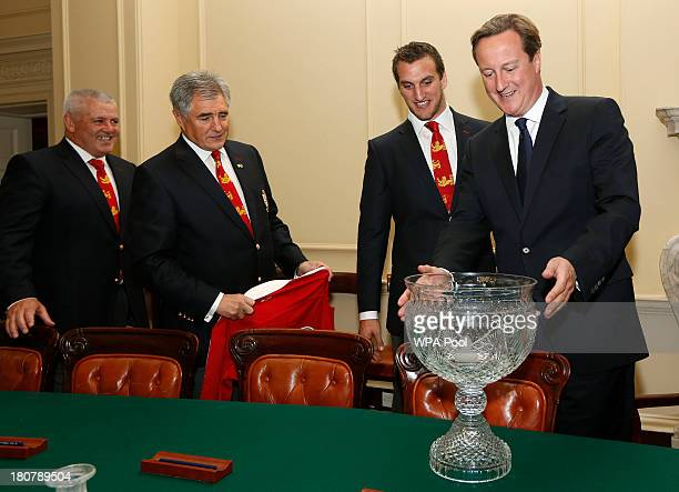 British Prime Minister David Cameron looks at the trophy as head coach Warren Gatland tour manager Andy Irvine and tour captain Sam Warburton watch...