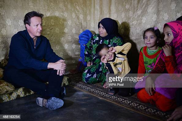 British Prime Minister David Cameron meets Syrian refugee families at a tented settlement camp on September 14 2015 in the Bekaa Valley on the Syrian...