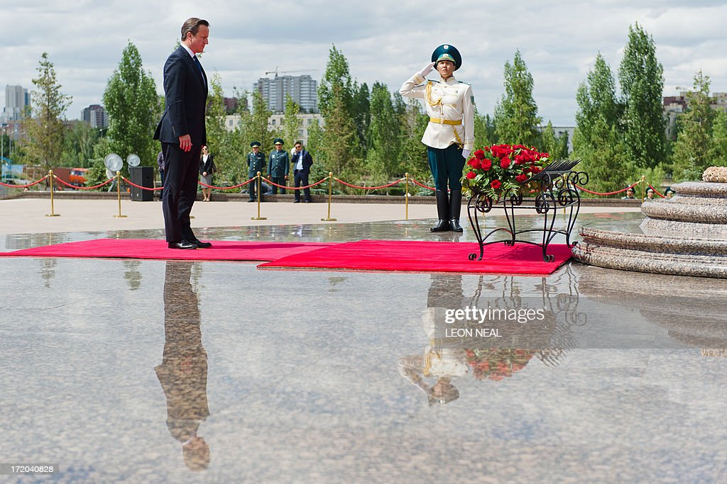 British Prime Minister David Cameron (L) pays his respects after laying a wreath at the Monument of the Motherland Defenders in Astana, Kazakhstan on July 1, 2013. David Cameron arrived in Kazakhstan on June 30, 2013 on the first ever trip by a serving British prime minister, hoping to boost trade ties but also promising to raise human rights concerns.