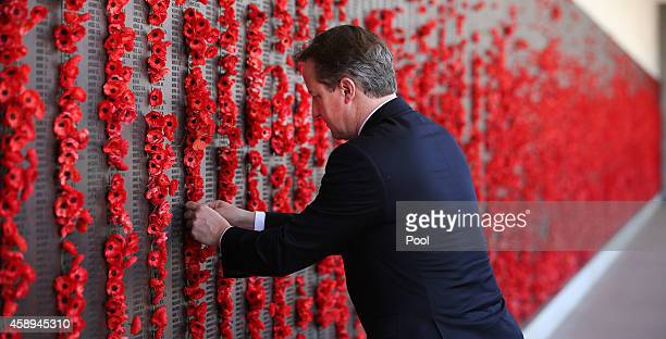 British Prime Minister David Cameron places a poppy along the Roll of Honour in the cloisters at the Australian War Memorial on November 14 2014 in...