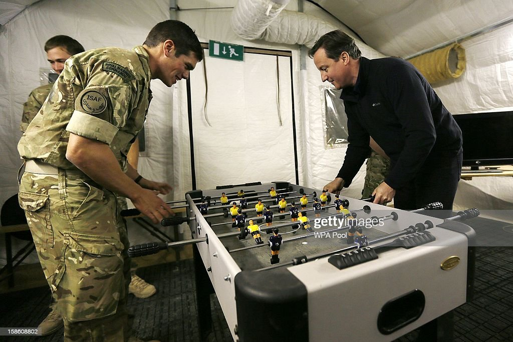British Prime Minister <a gi-track='captionPersonalityLinkClicked' href=/galleries/search?phrase=David+Cameron+-+Politician&family=editorial&specificpeople=227076 ng-click='$event.stopPropagation()'>David Cameron</a> (R) plays table football with a Royal Marine during a visit to Forward Operating Base Price on December 20, 2012 in Helmand Province, Afghanistan. Prime Minister Cameron is making a Christmas visit to British troops in the region amid tight security.