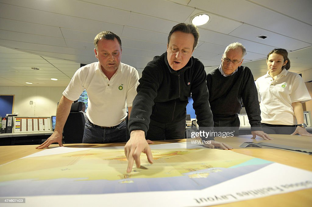 British Prime Minister David Cameron (C) points at a position on a map during a tour of the BP ETAP (Eastern Trough Area Project) oil platform in the North Sea with Offshore Installation manager Mark Furness (L) BP Regional president North Sea Trevor Garlick (R) on February 24, 2014, around 100 miles east of Aberdeen, Scotland. The British cabinet will meet in Scotland for only the third time in history to announce plans for the country's oil industry, which it warns will decline if Scots vote for independence. The fate of North Sea oil revenues will be a key issue ahead of the September 18 referendum to decide whether Scotland will end its 300-year-old union with England, and is expected to be the focus of Prime Minister David Cameron's cabinet meeting.