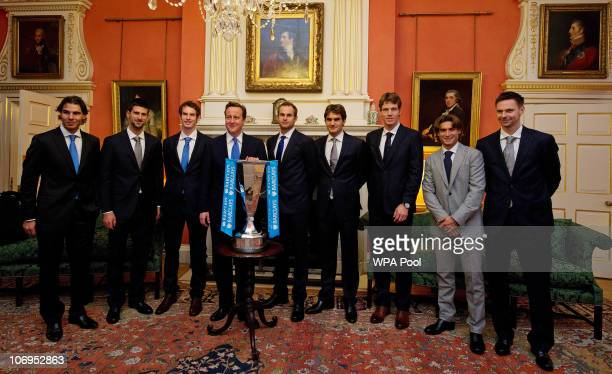 British Prime Minister David Cameron poses in front of the ATP World Tour Finals trophy with contenders Rafael Nadal of Spain Novak Djokovic of...