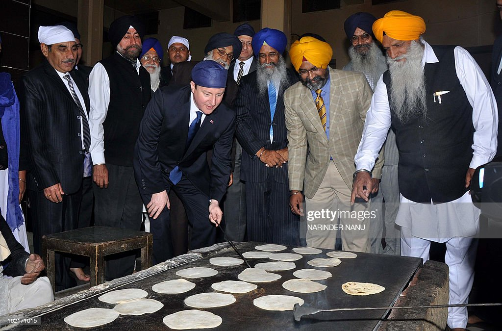 British Prime Minister David Cameron (C) prepares chapati for a communal vegetarian meal at a community kitchen during his visit to the Sikh Shrine Golden temple in Amritsar on February 20, 2013. British Prime Minister David Cameron visited the site of a colonial-era massacre in India during his visit to Amritsar, describing the episode as 'deeply shameful' while stopping short of a public apology. On the last leg of a three-day trip aimed at forging deeper economic ties, Cameron took the bold decision to visit the city of Amritsar. AFP PHOTO/ NARINDER NANU