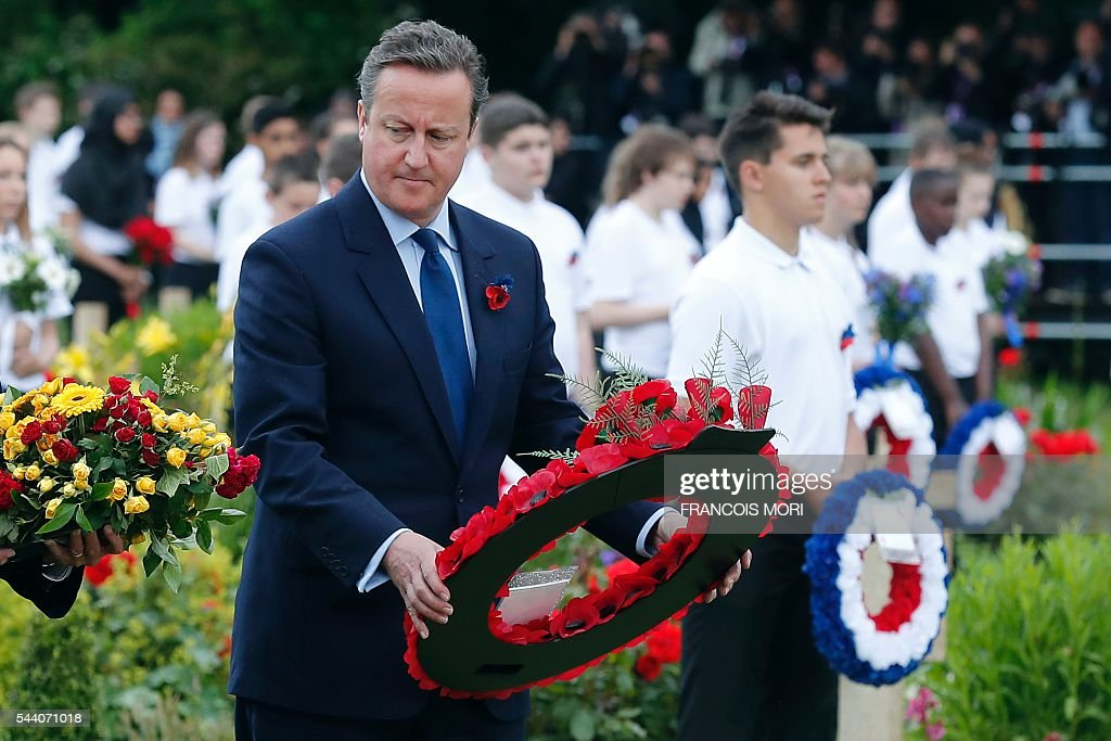 British Prime Minister David Cameron prepares to lay a apray of flowers as he attends the memorial ceremony on July 1, 2016, at the Thiepval Memorial in Thiepval, during which Britain and France will mark the 100 years since soldiers emerged from their trenches to begin one of the bloodiest battles of World War I (WWI) at the River Somme. Under grey skies, unlike the clear sunny day that saw the biggest slaughter in British military history a century ago, the commemoration kicked off at the deep Lochnagar crater, created by the blast of mines placed under German positions two minutes before the attack began at 7:30 am on July 1, 1916. / AFP / POOL / Francois Mori