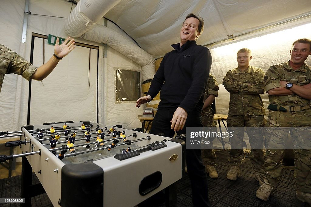 British Prime Minister <a gi-track='captionPersonalityLinkClicked' href=/galleries/search?phrase=David+Cameron+-+Politician&family=editorial&specificpeople=227076 ng-click='$event.stopPropagation()'>David Cameron</a> reacts as he plays table football with a Royal Marine during a visit to Forward Operating Base Price on December 20, 2012 in Helmand Province, Afghanistan. Prime Minister Cameron is making a Christmas visit to British troops in the region amid tight security.