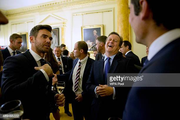 British Prime Minister David Cameron second right laughs as he chats with England bowler Jimmy Anderson left flanked by captain Alastair Cook right...