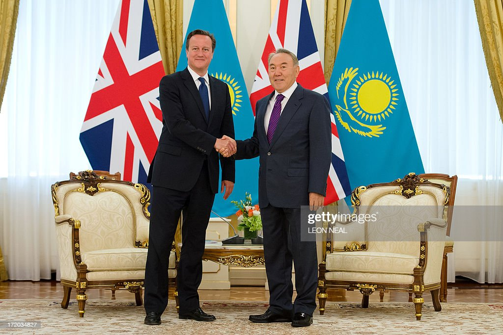 British Prime Minister David Cameron (L) shakes hands with Kazakhstan President Nursultan Nazarbayev (R) after arriving at the Presidential Palace in Astana, Kazakhstan on July 1, 2013. David Cameron arrived in Kazakhstan on June 30, 2013 on the first ever trip by a serving British prime minister, hoping to boost trade ties but also promising to raise human rights concerns. AFP PHOTO/POOL/ LEON NEAL