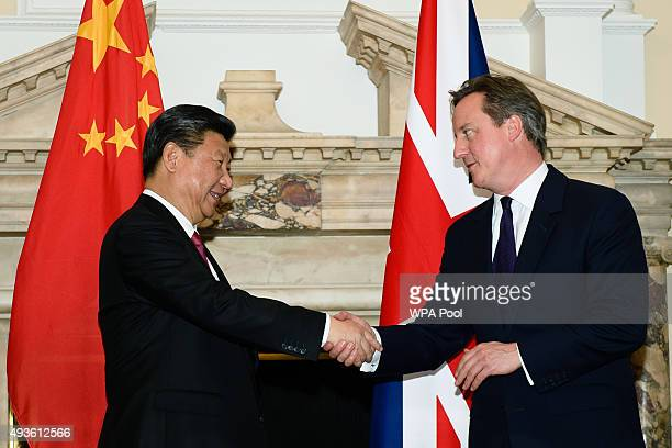British Prime Minister David Cameron shakes hands with the President of the People's Republic of China Xi Jinping during a commercial contract...