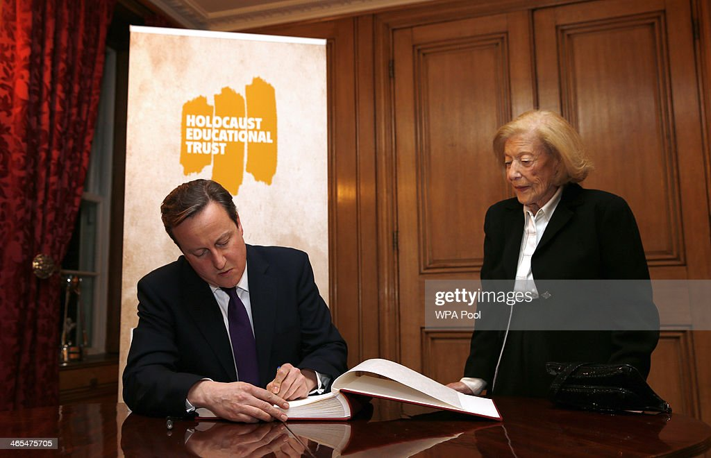 British Prime Minister David Cameron signs a book of commitment for the Holocaust Educational Trust during a reception for survivors of the Holocaust to commemorate International Holocaust Remembrance Day at 10 Downing Street on January 27, 2014, in London, England. The Prime Minister has announced that actress Helena Bonham Carter, broadcaster Natasha Kaplinsky, chief rabbi Ephraim Mirvis and a selection of politicians and businessmen will sit on the Holocaust Commission, which will discuss ways to ensure future generations will not forget the events of the Holocaust.