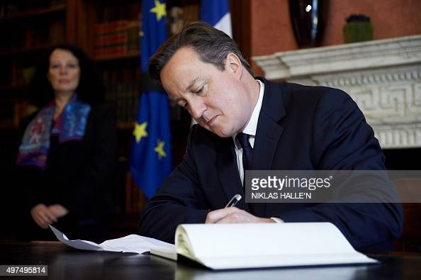 British Prime minister David Cameron signs a book of condolences at the French Ambassador's residence in London following last week's attacks in...