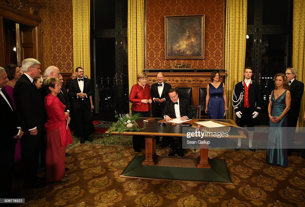 British Prime Minister <a gi-track='captionPersonalityLinkClicked' href=/galleries/search?phrase=David+Cameron+-+Politician&family=editorial&specificpeople=227076 ng-click='$event.stopPropagation()'>David Cameron</a> (C) signs the Golden Book of Hamburg as German Chancellor <a gi-track='captionPersonalityLinkClicked' href=/galleries/search?phrase=Angela+Merkel&family=editorial&specificpeople=202161 ng-click='$event.stopPropagation()'>Angela Merkel</a> (L) Hamburg's Mayor <a gi-track='captionPersonalityLinkClicked' href=/galleries/search?phrase=Olaf+Scholz&family=editorial&specificpeople=2162609 ng-click='$event.stopPropagation()'>Olaf Scholz</a> (2L) and his wife Britta Ernst (R) look on during the annual Matthiae-Mahl dinner at Hamburg City Hall on February 12, 2016 in Hamburg, Germany. The two leaders are there on the invitation of Hamburg Mayor <a gi-track='captionPersonalityLinkClicked' href=/galleries/search?phrase=Olaf+Scholz&family=editorial&specificpeople=2162609 ng-click='$event.stopPropagation()'>Olaf Scholz</a>, who reportedly saw the dinner as a gesture to show Germany's hope that Great Britain will remain in the European Union. The Matthiae-Mahl is a Hamburg tradition dating back to 1356 and began as a fest to welcome the spring season and also to honor a foreign official.