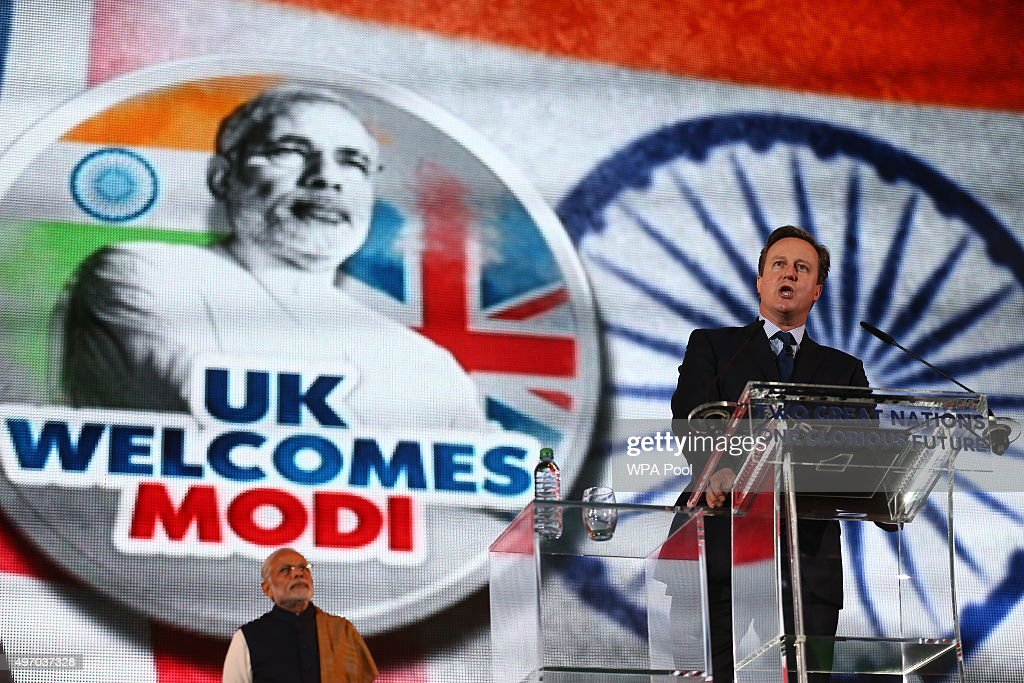 British Prime Minister David Cameron speaks as India's Prime Minister Narendra Modi looks on at Wembley Stadium during a welcome rally for Modi on November 13, 2015, in London, England. In his first trip to Britain as Prime Minister Modi's visit will aim to develop economic ties between the two countries. In a busy schedule he is due to speak at Wembley Stadium, have lunch with the Queen at Buckingham Palace, address Parliament and stay overnight at Chequers.