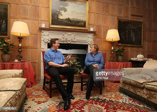 British Prime Minister David Cameron speaks with German Chancellor Angela Merkel at Chequers the Prime Minister's country residence on October 31...