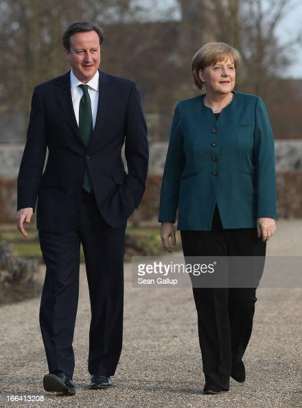 British Prime Minister David Cameron speaks with German Chancellor Angela Merkel during a stroll in the garden following his arrival at the Meseberg...