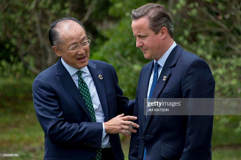 British Prime Minister David Cameron (R) speaks with World Bank President Jim Yong Kim (L) as they take part in the 'Outreach Session' family photo with world leaders at the G7 Summit in Shima in Mie prefecture on May 27, 2016. A British secession from the European Union in next month's referendum could have disastrous economic consequences, G7 leaders warned on May 27 at the close of the summit in Japan. / AFP / JIM