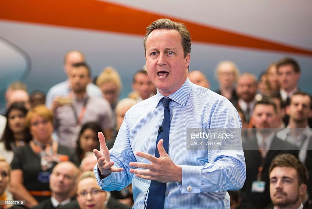 British Prime Minister David Cameron stands in front of an aircraft as he delivers a speech inside a hangar at low-cost airline EasyJet's headquarters in Luton, north of London on May 24, 2016. In a speech to workers, Cameron said 'If we were to leave, and the pound were to fall - which is what most people expect and what the Treasury forecast - that would put up the cost of a typical holiday for a family of four to a European destination by £230'. / AFP / Jack Taylor