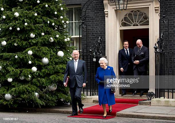 British Prime Minister David Cameron stands in the doorway as Britain's Queen Elizabeth II and Foreign Secretary William Hague walk together...