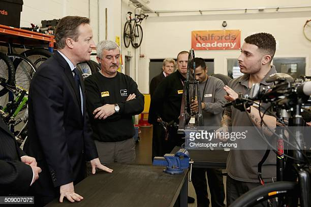 British Prime Minister David Cameron talks to inmate Chris inside the Halfords academy at HMP Onley where inmates are being trained to become...