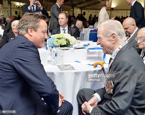 British Prime Minister David Cameron talks to veteran Ted MaslenJones who served as an Air Observer attached to the RAF in the Far East during a...