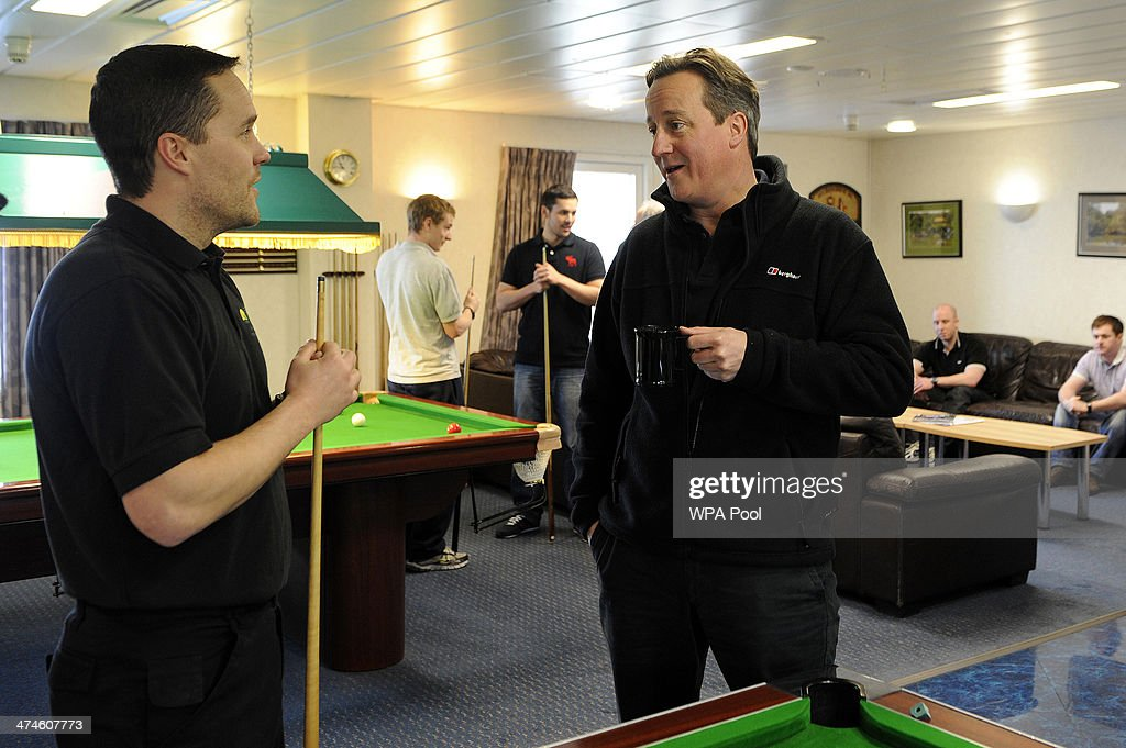 British Prime Minister David Cameron (L) talks with an employee during a tour of the BP ETAP (Eastern Trough Area Project) oil platform in the North Sea on February 24, 2014, around 100 miles east of Aberdeen, Scotland. The British cabinet will meet in Scotland for only the third time in history to announce plans for the country's oil industry, which it warns will decline if Scots vote for independence. The fate of North Sea oil revenues will be a key issue ahead of the September 18 referendum to decide whether Scotland will end its 300-year-old union with England, and is expected to be the focus of Prime Minister David Cameron's cabinet meeting.