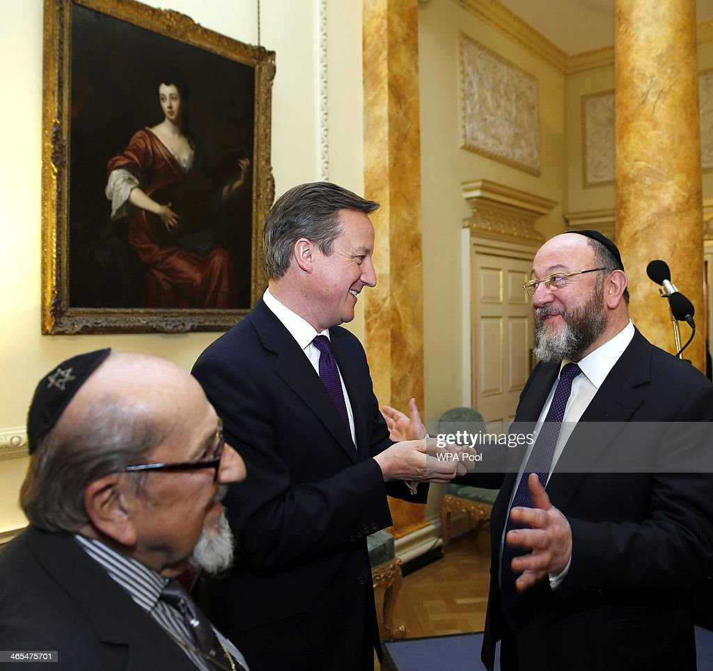 British Prime Minister David Cameron (C) talks with Chief Rabbi Ephraim Mirvis (R) during a reception for survivors of the Holocaust to commemorate International Holocaust Remembrance Day at 10 Downing Street on January 27, 2014, in London, England. The Prime Minister has announced that actress Helena Bonham Carter, broadcaster Natasha Kaplinsky, chief rabbi Ephraim Mirvis and a selection of politicians and businessmen will sit on the Holocaust Commission, which will discuss ways to ensure future generations will not forget the events of the Holocaust.