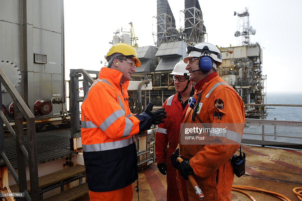 British Prime Minister David Cameron (L) talks with employees during a tour of the BP ETAP (Eastern Trough Area Project) oil platform in the North Sea on February 24, 2014, around 100 miles east of Aberdeen, Scotland. The British cabinet will meet in Scotland for only the third time in history to announce plans for the country's oil industry, which it warns will decline if Scots vote for independence. The fate of North Sea oil revenues will be a key issue ahead of the September 18 referendum to decide whether Scotland will end its 300-year-old union with England, and is expected to be the focus of Prime Minister David Cameron's cabinet meeting.