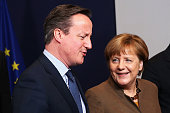 British Prime Minister David Cameron talks with German Chancellor Angela Merkel as they attend a group photo at the Council of the European Union on...
