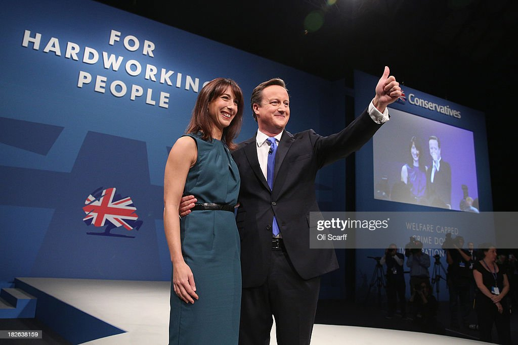 British Prime Minister <a gi-track='captionPersonalityLinkClicked' href=/galleries/search?phrase=David+Cameron+-+Politician&family=editorial&specificpeople=227076 ng-click='$event.stopPropagation()'>David Cameron</a> thanks the audience with his wife Samantha after delivering his keynote speech on the last day of the annual Conservative Party Conference at Manchester Central on October 2, 2013 in Manchester, England. During his closing speech <a gi-track='captionPersonalityLinkClicked' href=/galleries/search?phrase=David+Cameron+-+Politician&family=editorial&specificpeople=227076 ng-click='$event.stopPropagation()'>David Cameron</a> will say that his 'abiding mission' would make the UK into a 'land of opportunity'.