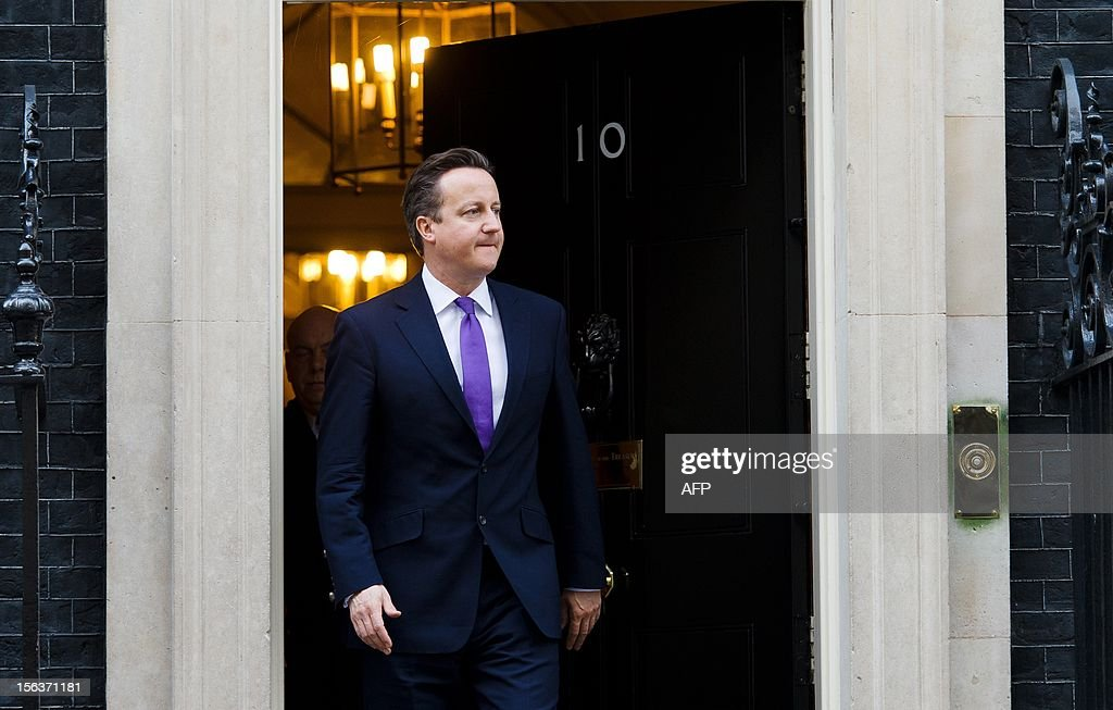 British Prime Minister David Cameron waits to greet his Thai counterpart Yingluck Shinawatra (not pictured) on the steps of number 10, Downing Street in central London on November 14, 2012. Yingluck Shinawatra is on an official visit to Britain during which she has met with Queen Elizabeth II and Prime Minister David Cameron. AFP PHOTO / LEON NEAL