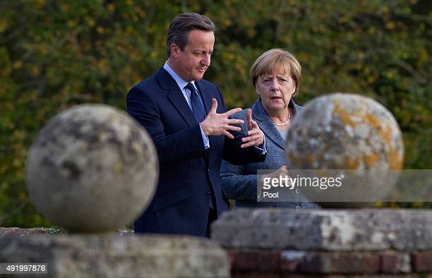 British Prime Minister David Cameron walks around the rose garden with German Chancellor Angela Merkel during a meeting at Chequers the Prime...