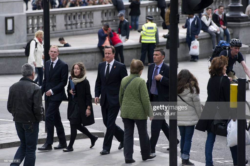 British Prime Minister David Cameron (C) walks in Trafalgar Square before going to St Martin-in-the-Fields Church in central London on April 22, 2013 to attend a memorial marking the 20th anniversary of teenager Stephen Lawrence's death. Lawrence, 18, was murdered by a gang of racists who stabbed him as he waited for a bus in Eltham, south-east London on April 22, 1993. PHOTO