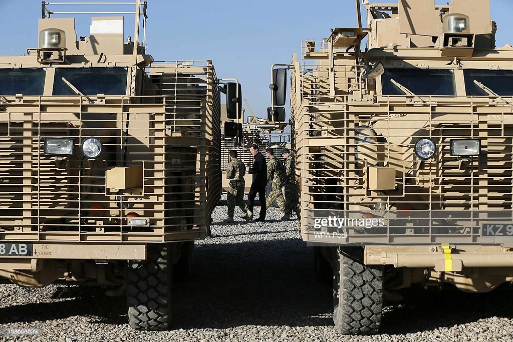 British Prime Minister David Cameron walks past Mastiff armoured vehicles as he talks with soldiers at Camp Bastion, outside Lashkar Gah on December 20, 2012 in Helmand Province, Afghanistan. Prime Minister Cameron is making a Christmas visit to British troops in the region amid tight security.