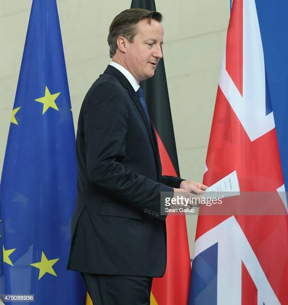 British Prime Minister David Cameron walks past the flags of the European Union and the United Kingdom as he arrives to speak to the media with...