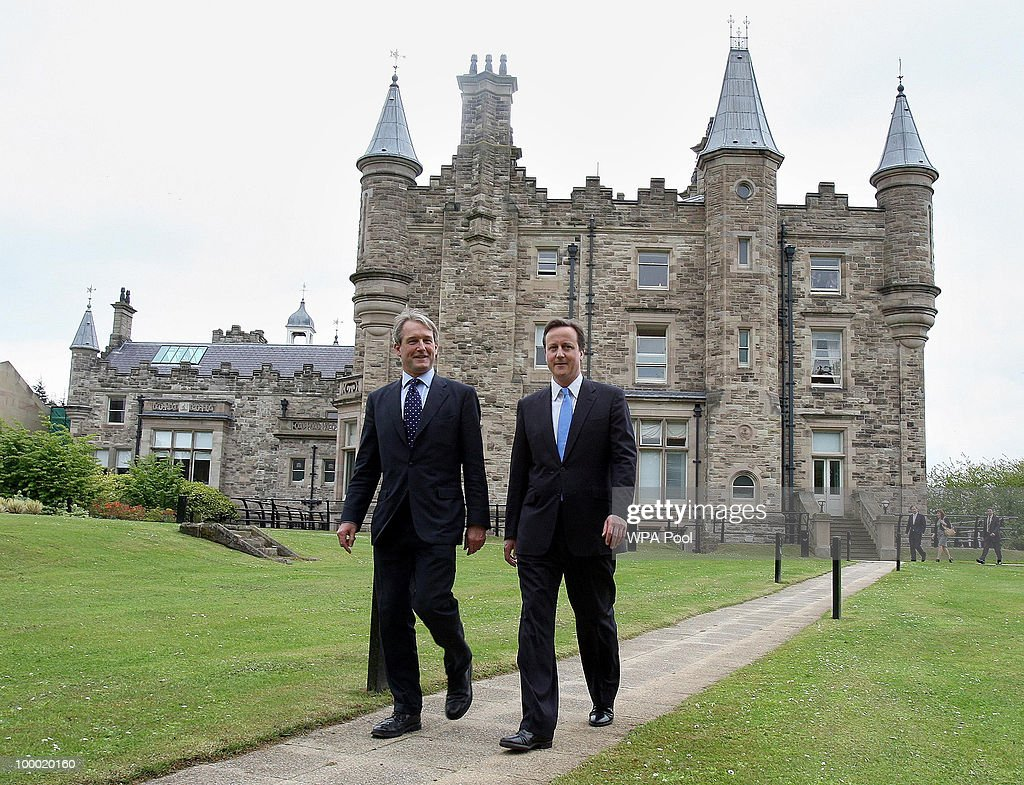 British Prime Minister David Cameron walks with Secretary of State for Northern Ireland Owen Paterson at Stormont Castle on May 20 2010 in County...