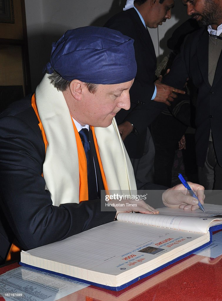 British Prime Minister <a gi-track='captionPersonalityLinkClicked' href=/galleries/search?phrase=David+Cameron+-+Politician&family=editorial&specificpeople=227076 ng-click='$event.stopPropagation()'>David Cameron</a> writing his comments on the visitor's book during his visit of Golden Temple, on February 20, 2013 in Amritsar, India.