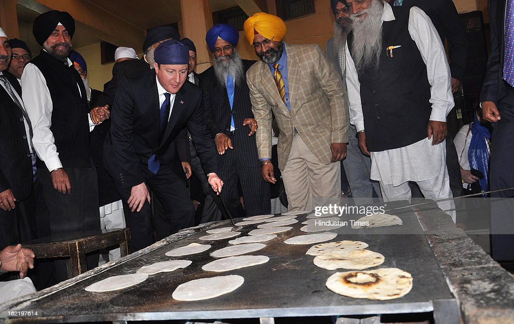British Prime Minister David Cameron's testing his hands in holy kitchen of Golden Temple during his visit, on February 20, 2013 in Amritsar, India.