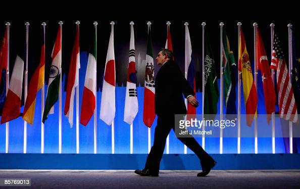 British Prime Minister Gordon Brown walks infornt of National flags at the G20 summit on April 2 2009 in London Mr Brown has announced a raft of...