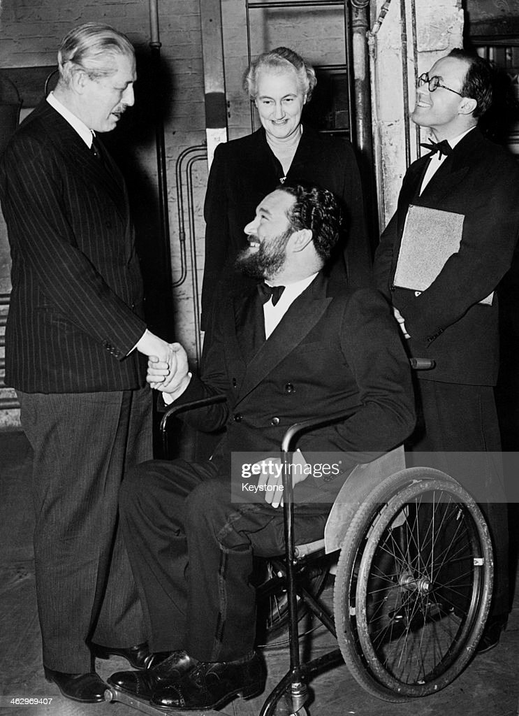 British Prime Minister <a gi-track='captionPersonalityLinkClicked' href=/galleries/search?phrase=Harold+Macmillan&family=editorial&specificpeople=201465 ng-click='$event.stopPropagation()'>Harold Macmillan</a> (1894 - 1986, left) congratulates English comic singing duo Michael Flanders (1922 - 1975, in wheelchair) and Donald Swann (1923 - 1994) after a performance of their revue 'At The Drop Of A Hat' at the Fortune Theatre, London, 1st March 1957. Looking on is the Prime Minister's wife, Lady Dorothy Macmillan (1900 - 1966).