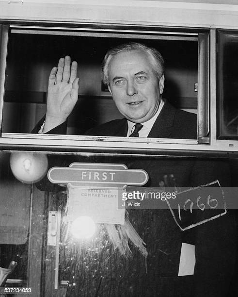 British Prime Minister Harold Wilson waving from the window of his train carriage on his way to his constituency in Huyton at Euston Station London...
