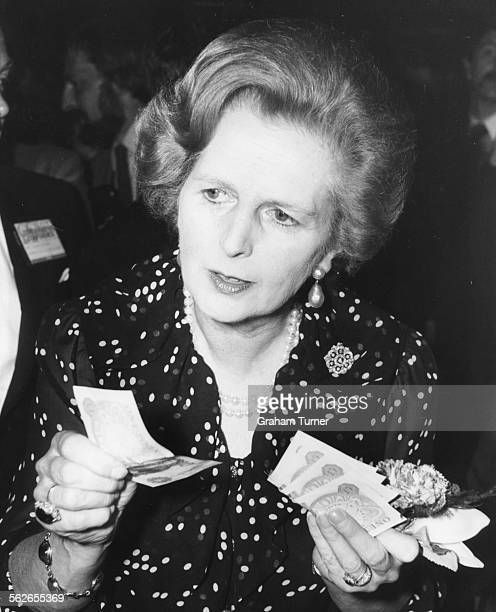 British Prime Minister Margaret Thatcher holding a handful of one pound notes at a Tombola stall during a celebration ball as part of the...