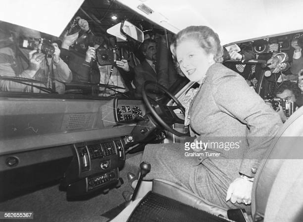 British Prime Minister Margaret Thatcher is surrounded by press photographers as she arrives in her Mini Metro car to open the Intentional Motor Show...