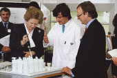 British Prime Minister Margaret Thatcher uses lab equipment as minister for Food and Agriculture John Selwyn Gummer and a member of staff look on...